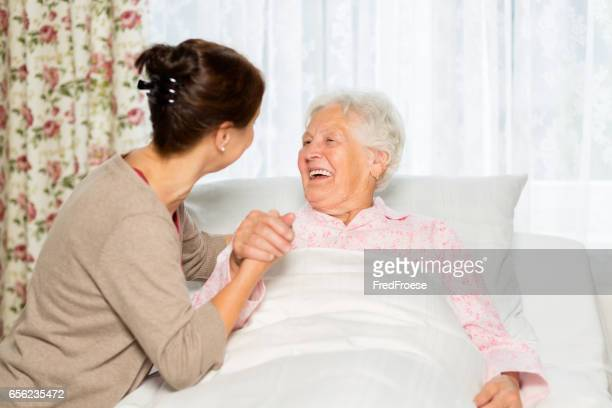 Caregiver and senior woman in bed at home