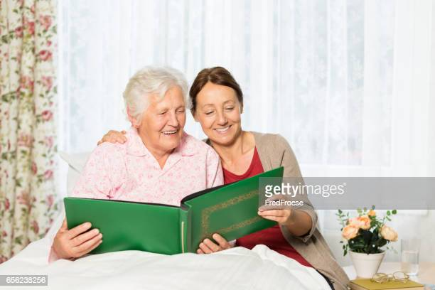 soignant et senior femme au lit à la maison - chambre hopital photos et images de collection