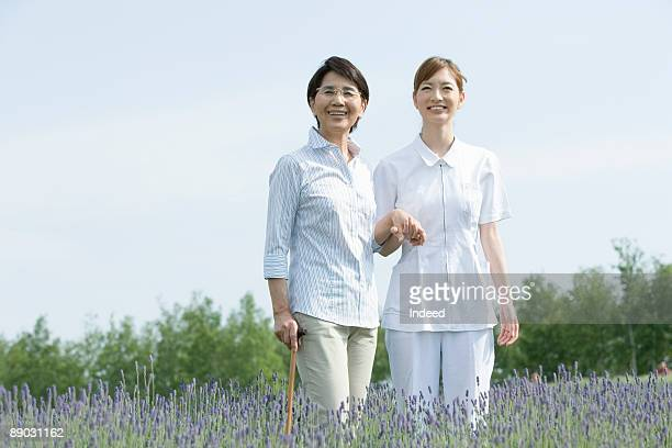 Caregiver and senior woman in lavender field
