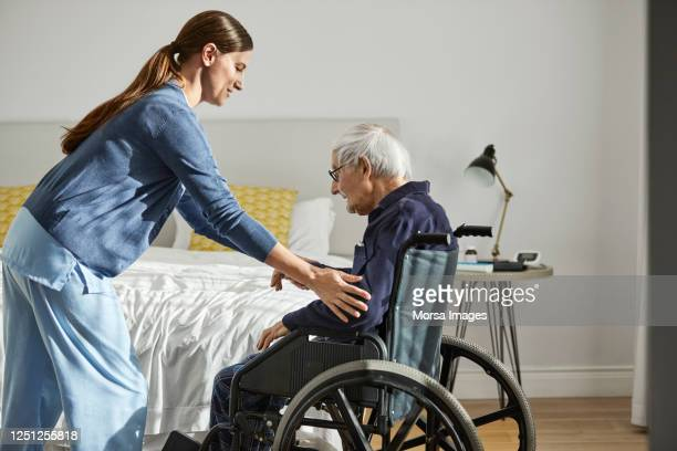 caregiver assisting senior man on wheelchair - fürsorglichkeit stock-fotos und bilder