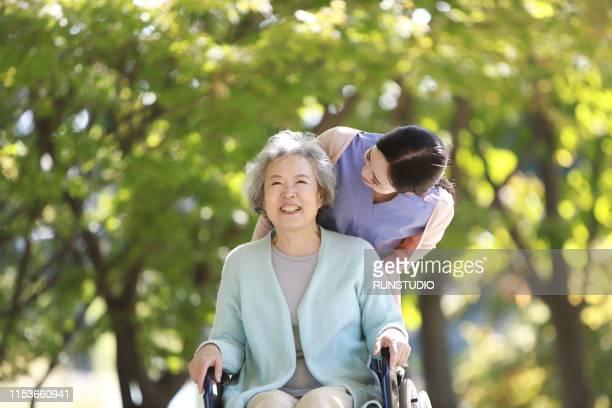 caregiver assisting senior woman in wheelchair - 老化 ストックフォトと画像