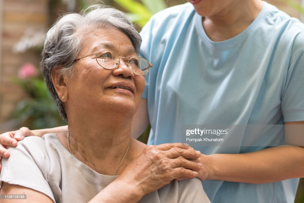 Caregiver, carer hand holding elder hand woman in hospice care. Philanthropy kindness to disabled concept.Public Service Recognition Week : Stock Photo