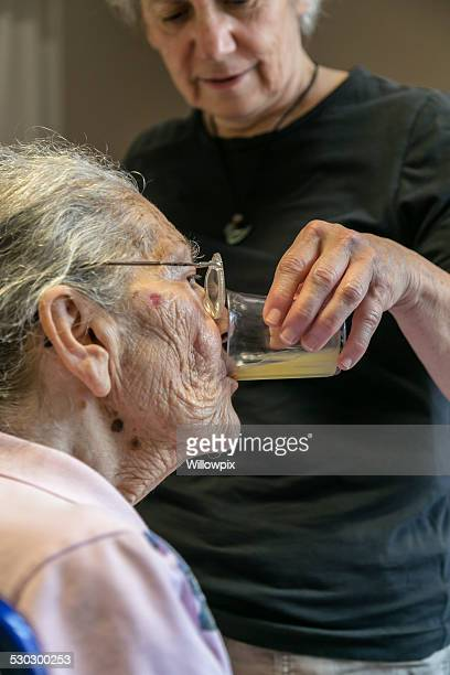 Caregiver Daughter Helping Elderly Dementia Woman Drink Juice