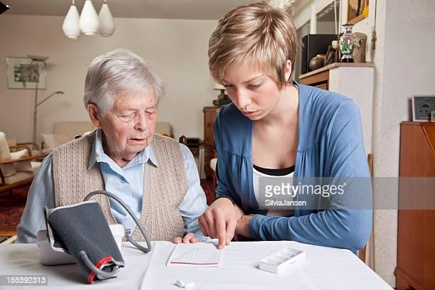 caregiver explaining blood pressure and medicine to senior woman