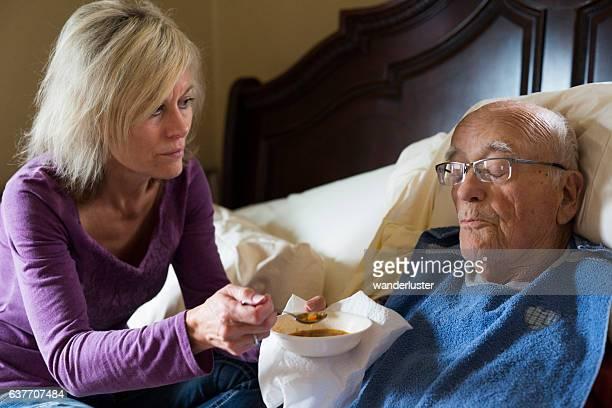 Caregiver feeds Dad soup