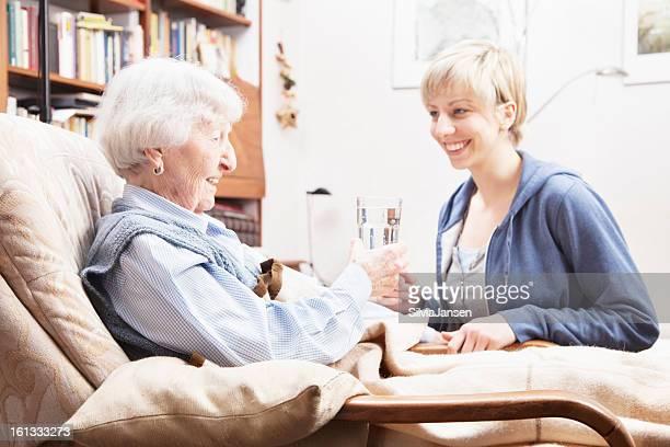 caregivergiving Glas Wasser senior Frau