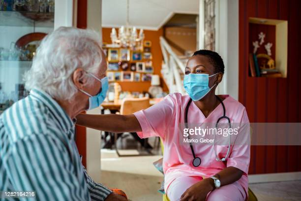 caregiver helping a senior man - essential services stock pictures, royalty-free photos & images