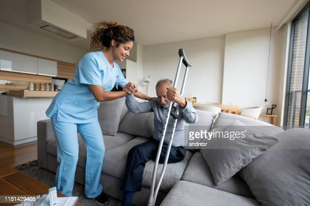 caregiver helping a senior man with a disability to stand up at home - diabetic amputation stock pictures, royalty-free photos & images