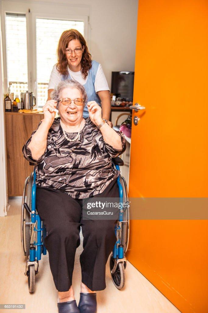 Pflegeperson helfen, eine ältere Frau auf einen Rollstuhl im Pflegeheim : Stock-Foto