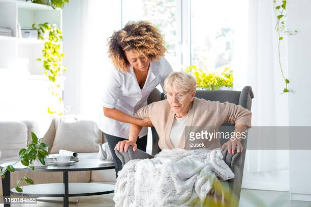 caregiver helping older lady to stand up - izusek stock pictures, royalty-free photos & images