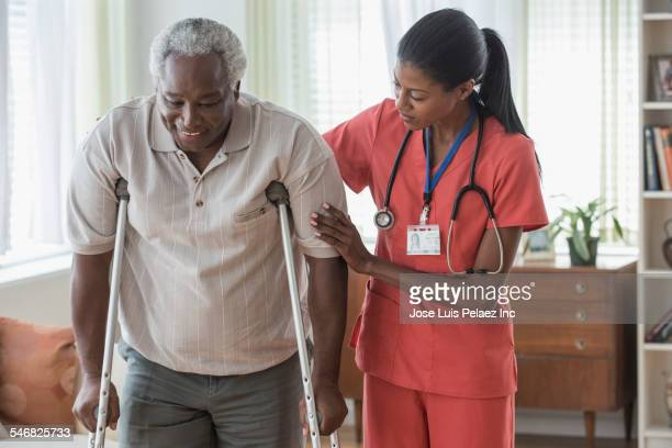 caregiver helping older man walk on crutches - crutches stock photos and pictures