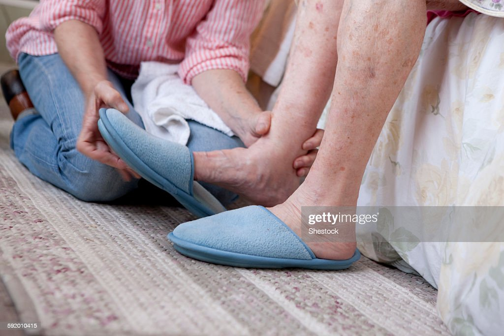 Caregiver helping older woman in home : Stock Photo