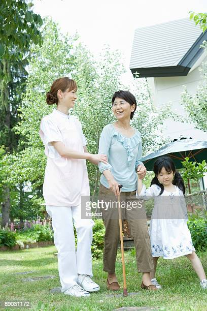 Caregiver helping senior woman walk with girl