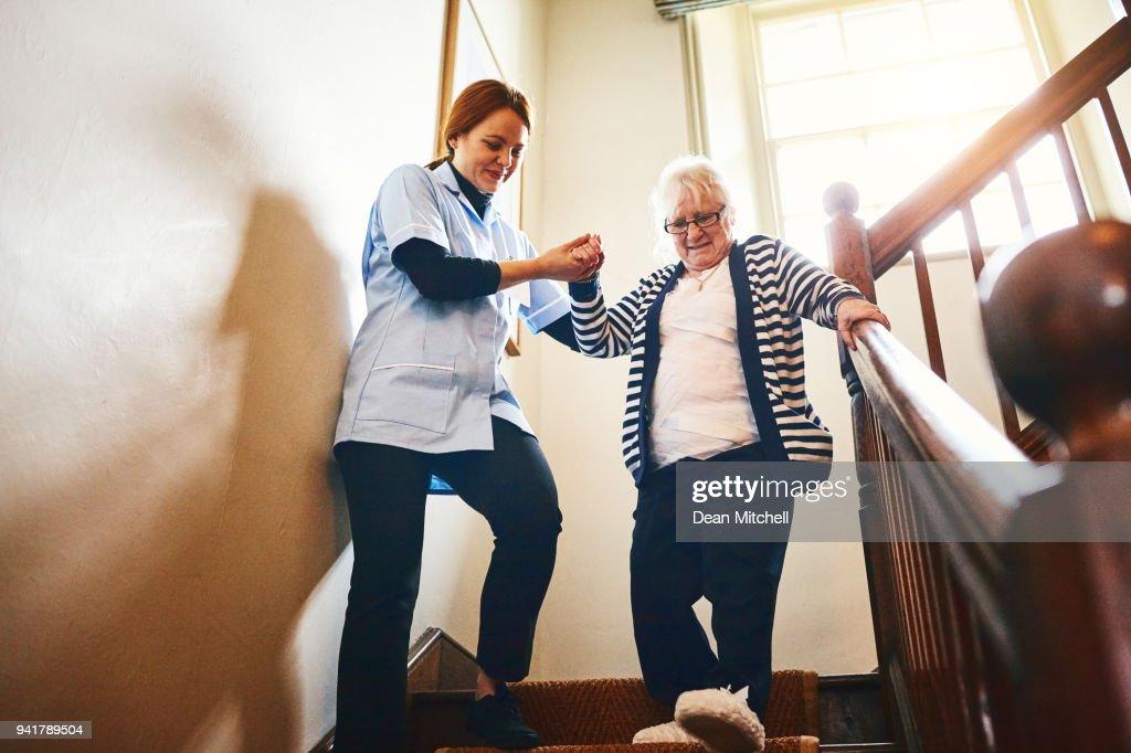 Verzorger helpen senior vrouw trap af lopen : Stockfoto