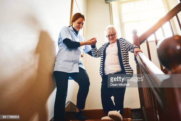 caregiver helping senior woman walking down stairs - social services stock pictures, royalty-free photos & images