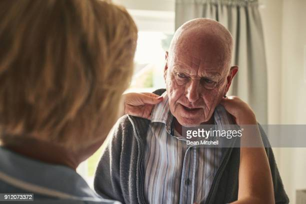 caregiver helps dressing elderly patient at home - getting dressed stock pictures, royalty-free photos & images