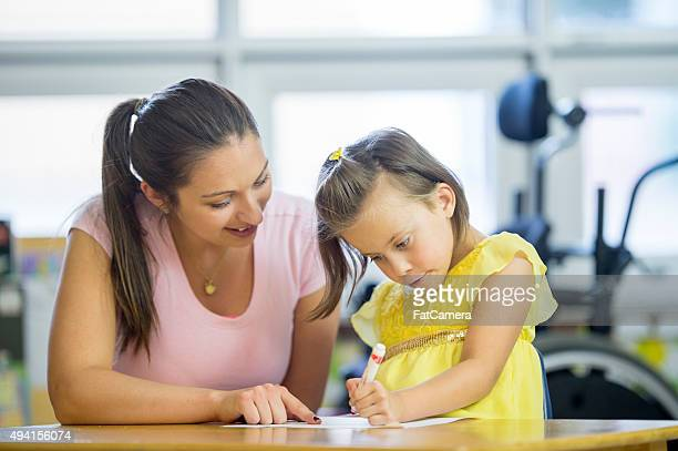 Caregiver is Showing a Little Girl Where to Color