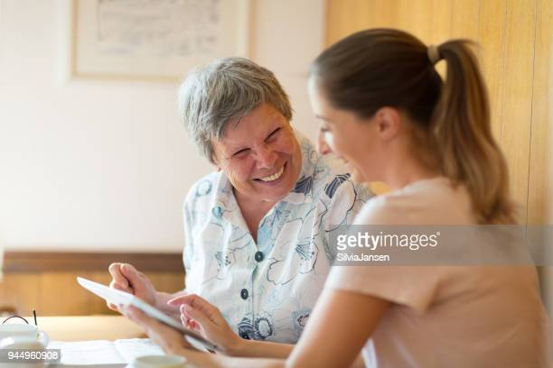 caregiver showing digital tablet to senior woman - caregiver stock pictures, royalty-free photos & images