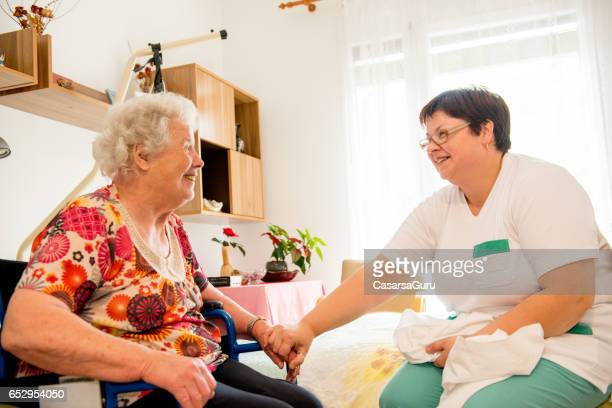 caregiver socializing with senior woman while cleaning her room - residential care stock photos and pictures
