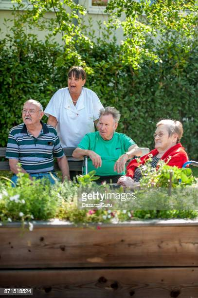 caregiver socializing with seniors at the backyard of the retirement community - residential care stock photos and pictures