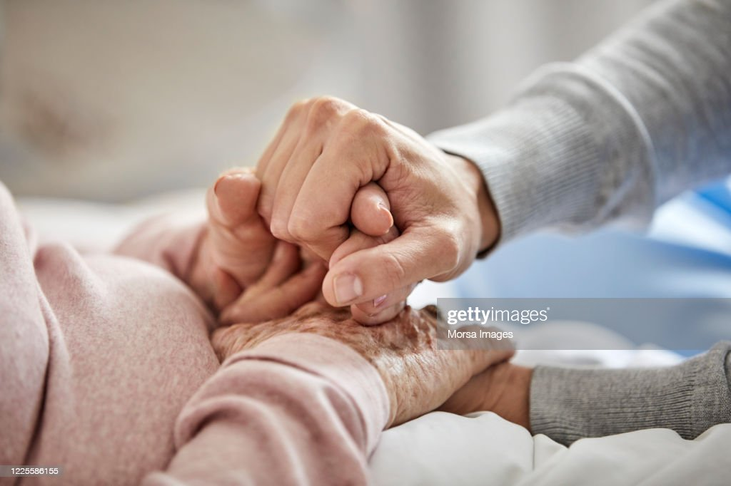 Caregiver supporting woman during corona outbreak : Stockfoto