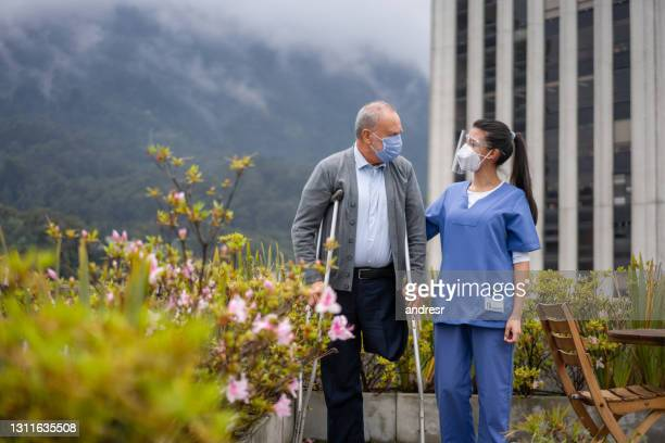 caregiver taking a disabled man for an outdoor walk during the pandemic - fragility stock pictures, royalty-free photos & images