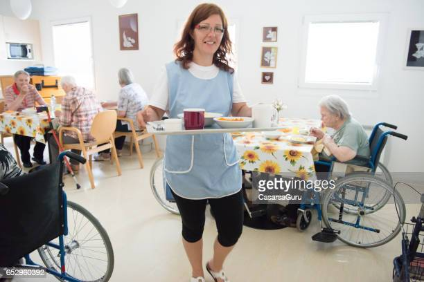 caregiver taking lunch to a senior woman in the room - residential care stock photos and pictures