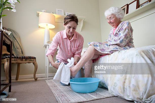 caregiver washing foot of older woman in bedroom - taking a bath stock pictures, royalty-free photos & images