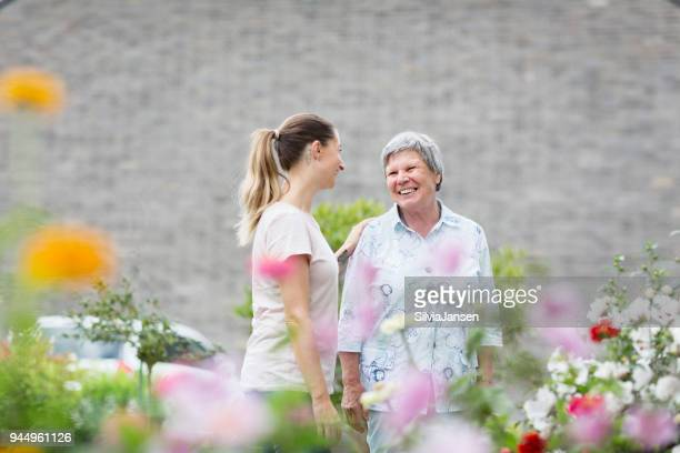 caregiver with senior adult outdoors in garden - janitorial services stock photos and pictures