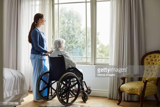 caregiver with senior woman looking through window - altersheim stock-fotos und bilder
