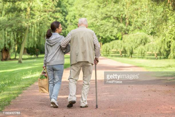 caregiver – woman helping senior man with shopping - walking cane stock pictures, royalty-free photos & images