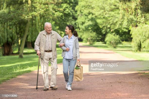 caregiver – woman helping senior man with shopping - african american man helping elderly stock pictures, royalty-free photos & images
