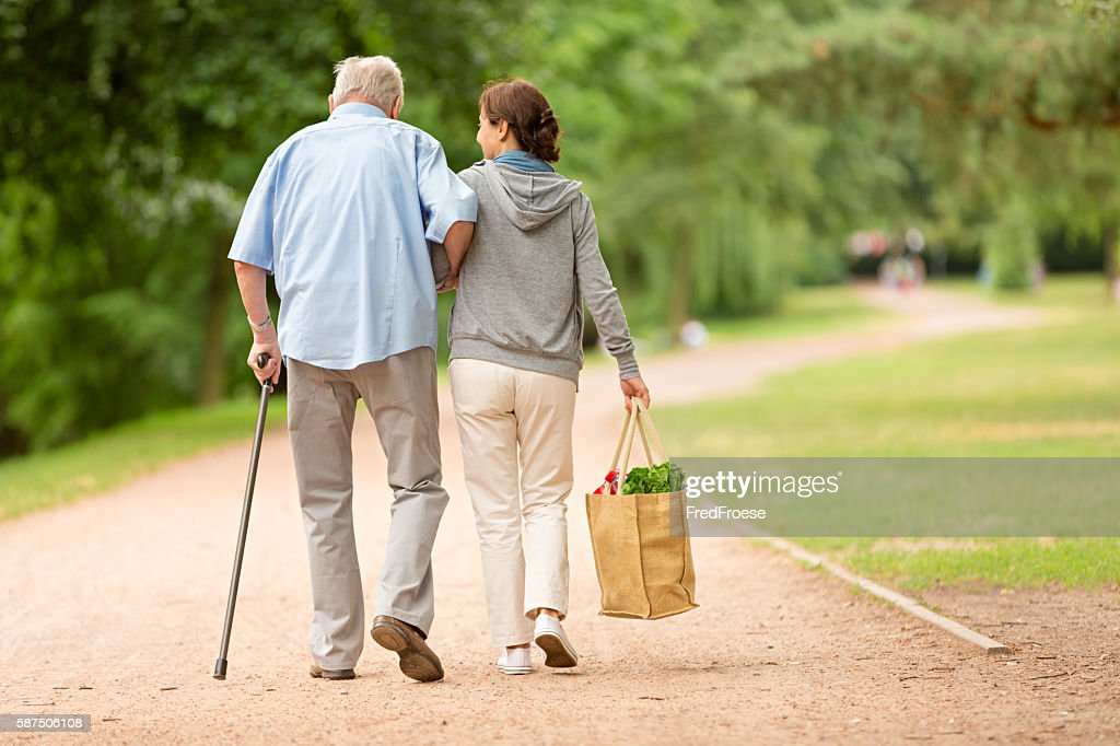 Caregiver – woman helping senior man with shopping : Stockfoto