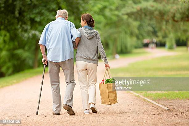 caregiver – woman helping senior man with shopping - gezondheidszorg beroep stockfoto's en -beelden