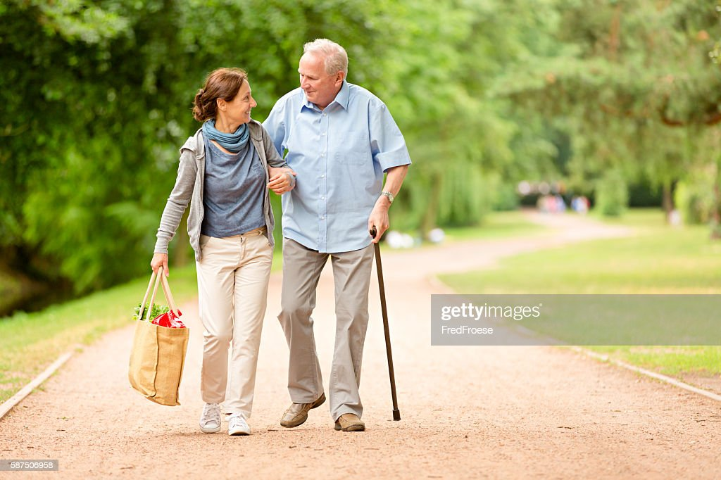 Caregiver – woman helping senior man with shopping : Stock Photo
