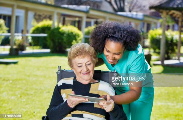 caregivers at home. disabled elderly lady showing photos of her grandchildren on tablet to caregiver - gerontology stock pictures, royalty-free photos & images