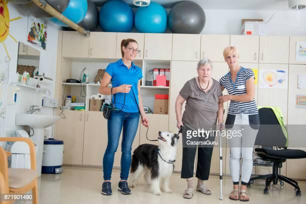 Soignants à femme Senior à marcher avec un chien dans la maison de retraite