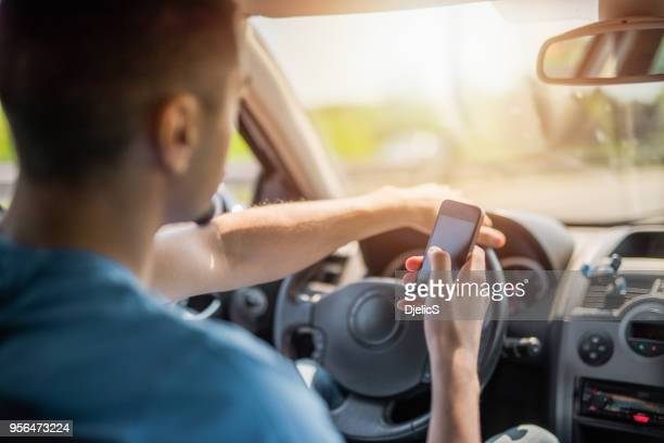 Careless young man texting a message while driving a car.