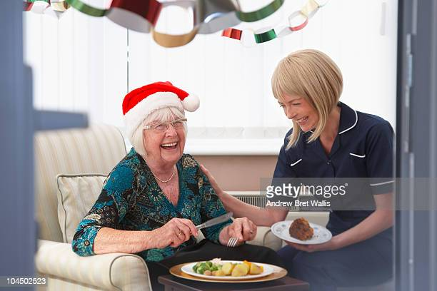 carer and elderly woman, at Christmas, laughing