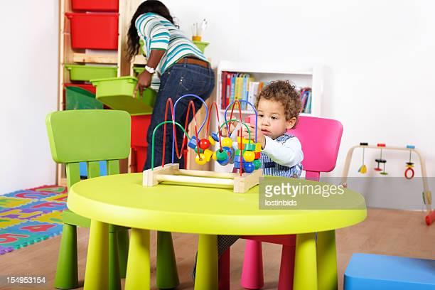 Carer/ Childminder/Parent Tidying While Toddler Plays