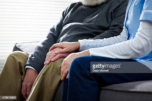 Carer consoling vieux homme assis ensemble