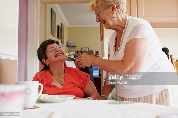 carer helping disabled woman to eat a meal