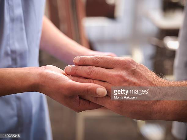 carer holding hand of senior man - affectionate stock pictures, royalty-free photos & images