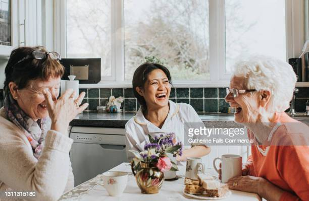 a carer laughs during a conversation with two older ladies at a kitchen table - senior adult stock pictures, royalty-free photos & images