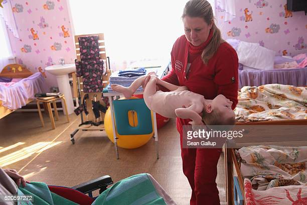 Carer Lyena Nazardenko employed by the Irish charity Chernobyl Children International carries Vasilii who was born with severe birth defects and is...