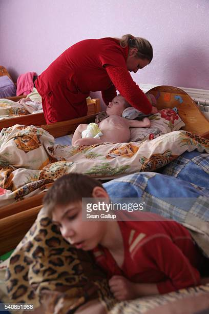 Carer Lyena Nazardenko employed by the Irish charity Chernobyl Children International prepares Vasilii who was born with severe birth defects and is...