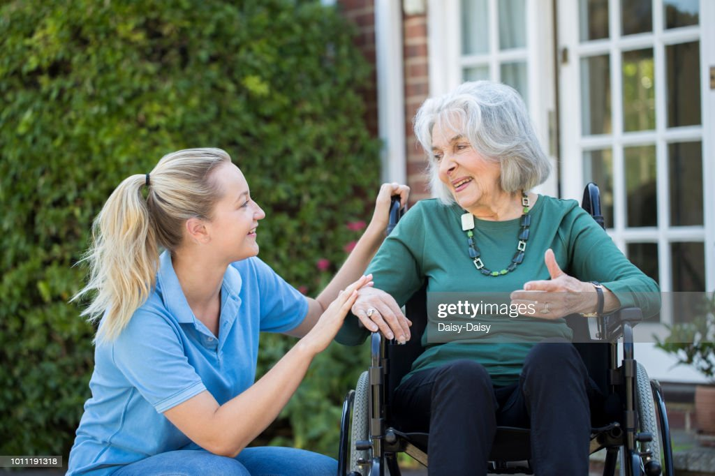 Carer Pushing Senior Woman In Wheelchair Outside Home : Stock Photo