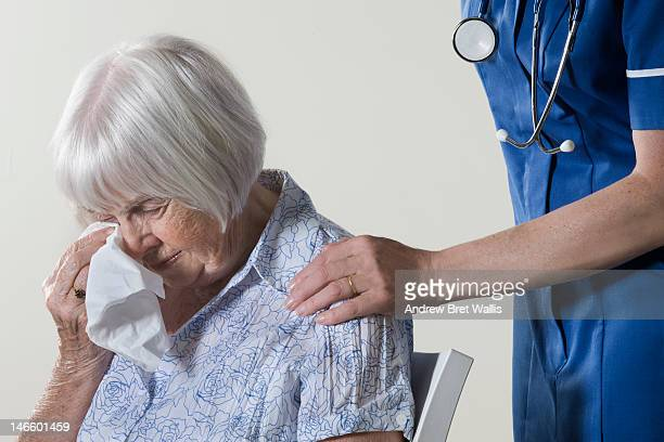 Carer reassures an upset senior woman