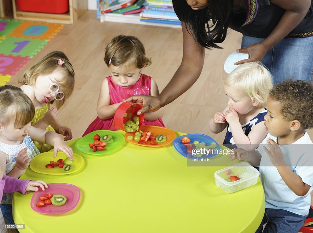 Carer Serving Fruit To Group Of Toddlers/ Children At Nursery : Stock Photo