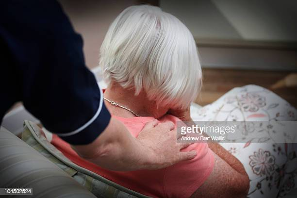 Carer supporting a grieving elderly woman at home
